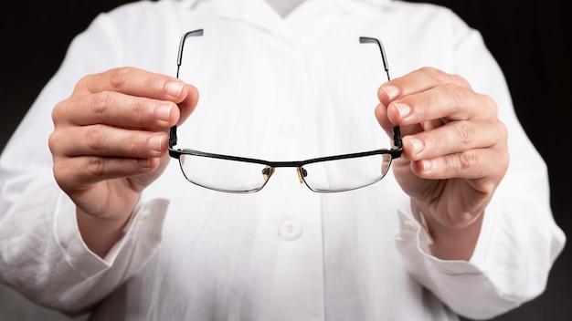 Врач-оптик дает пациенту очки для улучшения зрения.