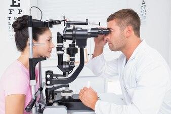 Optician examining womans eyes through slit lamp