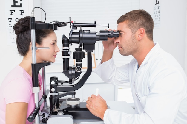 Optician examining womans eyes through slit lamp