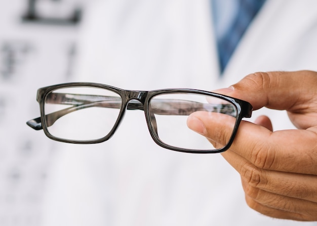 Optician holding eyeglasses with black frame