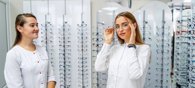 Optician is helping female client to choose glasses in optic shop