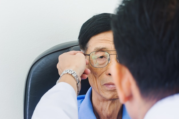 Optician male hands put glasses on elderly man testing his eye