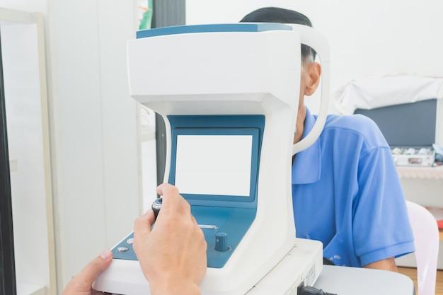 Руки optician мужские используя инструменты для проверять зрение и здоровье глаза изолированные на белизне.
