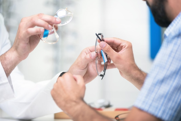 Optician offering glasses to customer for testing and trying