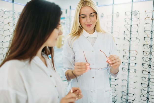 Optician shows glasses to customer in optics store