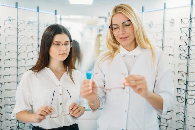 Оптик показывает очки покупателю в магазине оптики