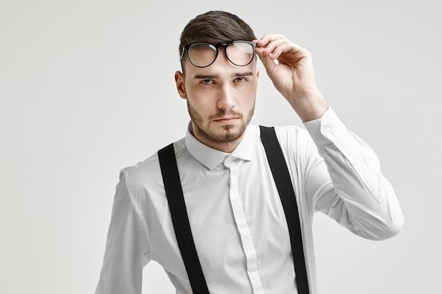 光学、アイウェア、ファッションのコンセプト。サスペンダー付きの白いフォーマルシャツを着て、精査した表情でカメラを見つめ、眼鏡を持ち上げているハンサムな無精ひげを生やした若いブルネットの男性の写真