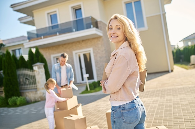 Optimism. beautiful smiling blonde woman with box walking to her husband and daughter standing near things near house looking back