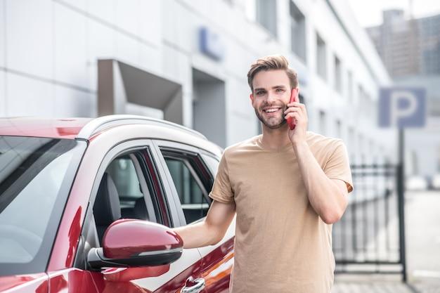 楽観。日中の街の通りで彼の赤い車の近くに立っている耳の近くにスマートフォンを持つうれしそうな若い大人の男