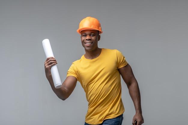 Оптимист. веселый молодой взрослый темнокожий мужчина в строительном ярком шлеме и желтой футболке с рулоном бумаги, активным движением