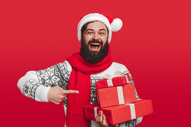 Optimistic adult bearded male in santa hat