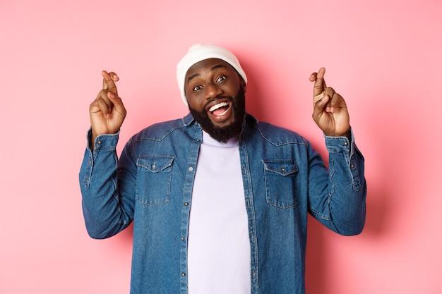 Uomo afroamericano ottimista che esprime desiderio, tenendo le dita incrociate e sorridendo, in piedi su sfondo rosa