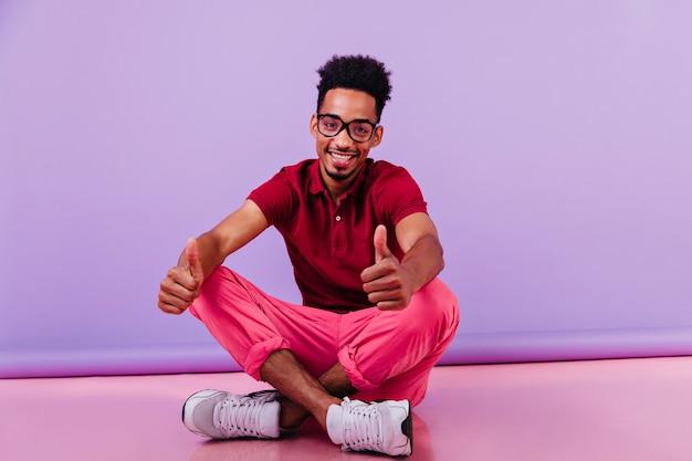다리를 건너 앉아 분홍색 바지에 낙관적 인 아프리카 남자. 바닥에 포즈 웃는 똑똑한 사람.