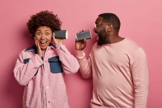 楽観的なアフリカ系アメリカ人の女性と男性は、耳と口の近くでコーヒーから紙コップを持ち、ピンクのパステルカラーの服を着て、叫び、笑い、浮気します