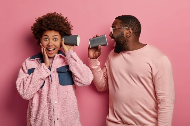 Uomo e donna afroamericani ottimisti tengono bicchieri di carta dal caffè vicino all'orecchio e alla bocca, indossano abiti rosa pastello, gridano e ridono, scherzano