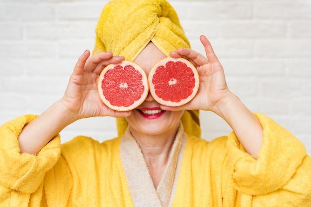 Оптимистичная стареющая дама, закрывающая глаза дольками грейпфрута, косметические процедуры