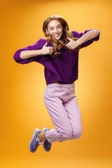 Оптимистичная и радостная яркая рыжая девушка весело и весело прыгает, показывая большие пальцы в знак лайка и одобряя, давая положительный отзыв о супер крутой идее или концепции над оранжевой стеной