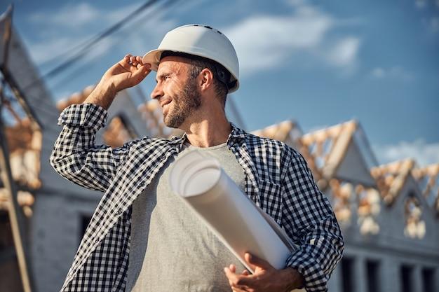新しい建物の青写真を運ぶ楽観的な建築家