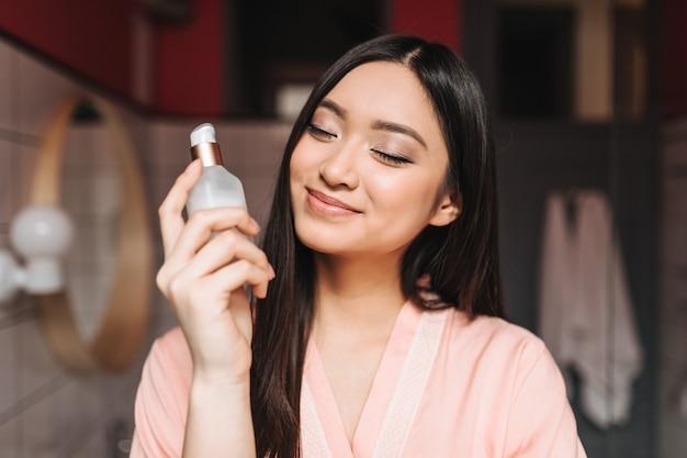 楽観的なアジアの女性は目を閉じて微笑んで、クリームの瓶を保持します