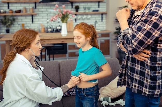 낙관적 인 태도. 건강 검진을받는 동안 좋은 기분에있는 긍정적 인 아픈 소녀