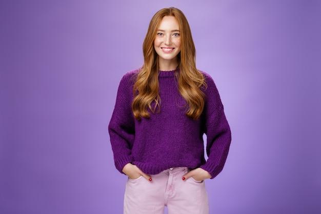 Ottimista attraente ragazza zenzero negli anni '20 che indossa un maglione viola in piedi pronta ed energica su sfondo viola sorridente amichevole e fiducioso alla macchina fotografica, mostrando disponibilità a divertirsi.