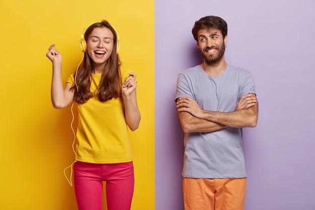 Оптимистичная привлекательная дама слушает музыку в наушниках, двигается, как слышит любимую песню, закрывает глаза от удовольствия, счастливый мужчина скрещивает руки