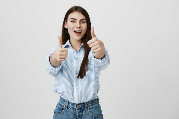 Optimistic attractive young woman showing thumb-up