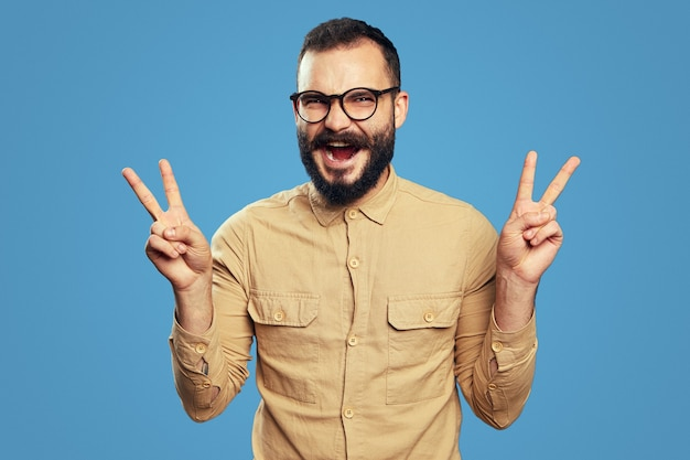 Optimistic bearded male screams and shows victory gesture with both hands