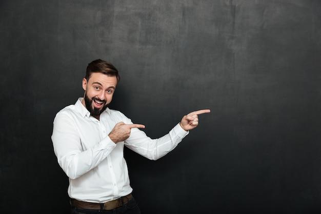 Оптимистичный бородатый мужчина в белой рубашке, указывая указательными пальцами в сторону, демонстрируя или рекламируя над темно-серой копией пространства