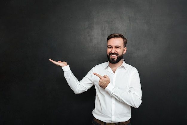 Optimistic bearded man pointing index finger while holding thing on palm, demonstrating or advertising over dark gray copy space