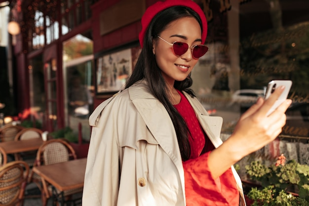 Optimistic brunette tanned woman in red beret, stylish dress and beige trench coat smiles, holds phone and takes selfie in street cafe