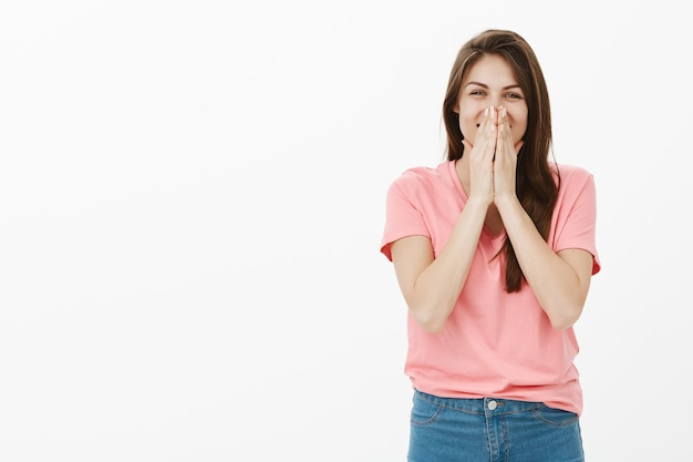Оптимистичная брюнетка женщина позирует в студии