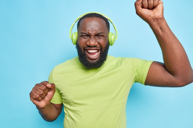 Optimistic carefree bearded man dances with rhythm of music dressed in green t shirt listens music isolated over blue wall