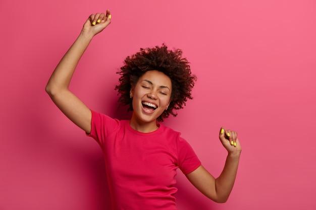 楽観的なのんきな巻き毛の若い女性は、腕を上げてお気に入りの素晴らしい音楽に合わせて踊り、歌のリズムに合わせて動き、ピンクの壁に隔離されたカジュアルなtシャツを着て、すべてのトラブルを忘れます