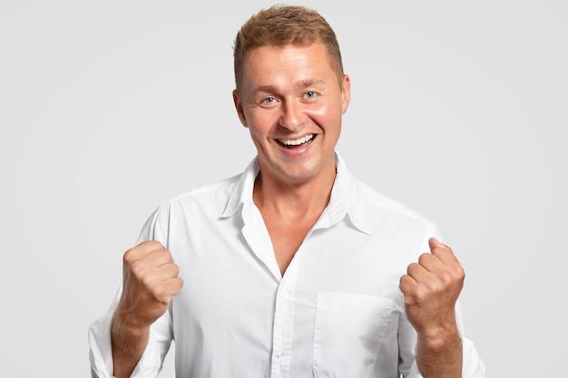 Оптимистичный жизнерадостный европейский мужчина с триумфом сжимает кулаки, празднует успех на работе, дружелюбно улыбается, одет в белую рубашку, позирует в помещении. успешный бизнесмен жесты крытый