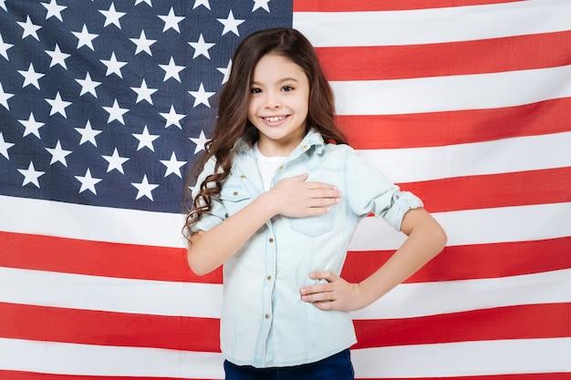 Оптимистичная веселая улыбающаяся девушка веселится и выражает радость, стоя против американского флага