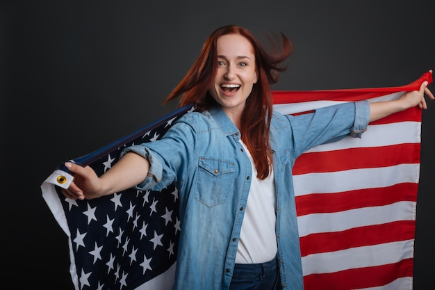 Оптимистичный гражданин. харизматичная гордая замкнутая дама, очень энергичная, делает патриотическую фотосессию и позирует изолированно на сером фоне