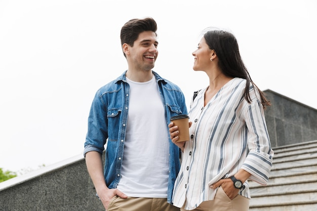 Optimistic couple man and woman with paper cup smiling and talking while strolling down stairs outdoors