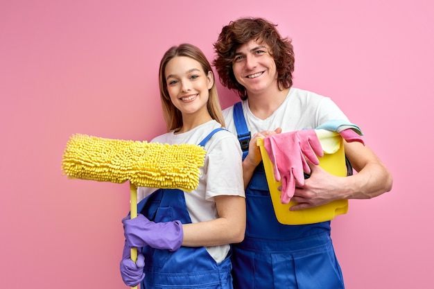 Optimistic couple use rags and other tools for cleaning, posing at camera isolated over pink background.