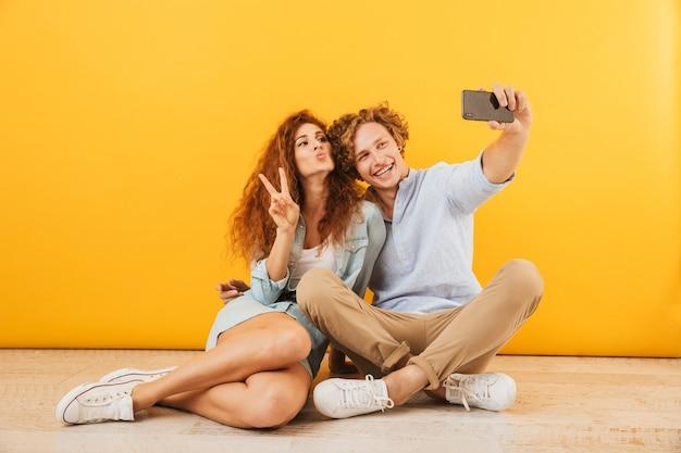 一緒に床に座って、黄色の背景で隔離のスマートフォンでselfieをしながらピースサインを示す楽観的なカップルの若い男性と女性