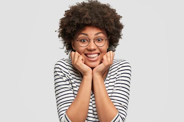 楽観的な巻き毛のアフリカ系アメリカ人の女性は、歯を見せる笑顔を持ち、あごの下に手を保ち、友人からの楽しい話を聞き、白い壁に隔離されたカジュアルな服と丸い眼鏡をかけています。