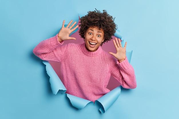 Оптимистичная кудрявая женщина поднимает ладони и в игривом настроении радостно смеется