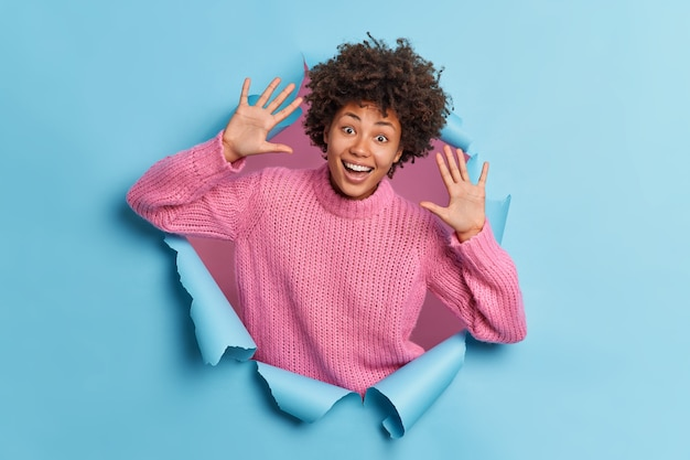 Optimistic curly haired woman raises palms and has playful mood laughs out happily