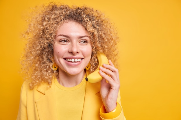 Optimistic curly haired woman smiles pleasantly holds banana near ear as if having telephone talk looks away with dreamy expression isolated over yellow wall copy space.