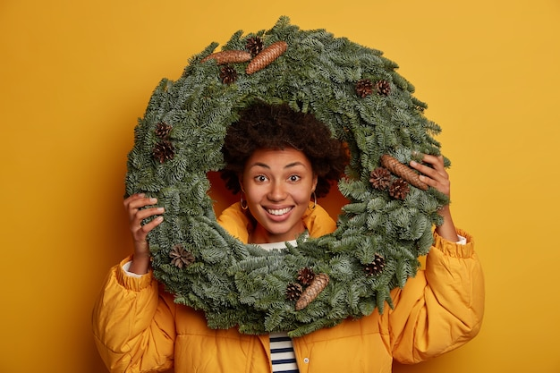 Optimistic curly woman looks through handmade christmas wreath, being in good mood, wears down padded coat, stands against yellow background.
