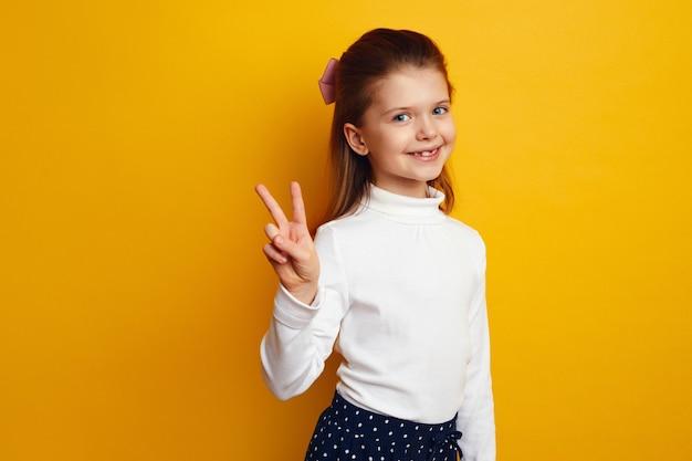 Оптимистичная милая девочка-ребенок показывает жест мира на ярко-желтом фоне