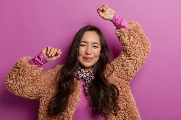 La ragazza dai capelli scuri ottimista tiene le braccia alzate, ha un'espressione felice e rilassata, celebra la vittoria, esulta per lo spazio viola, si diverte