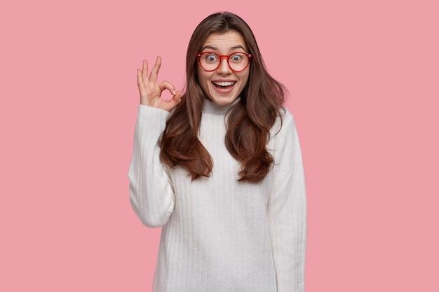 La giovane donna ottimista dai capelli scuri mostra il segno zero o il gesto giusto, sorride ampiamente, indossa un maglione bianco, approva tutto ciò che è buono