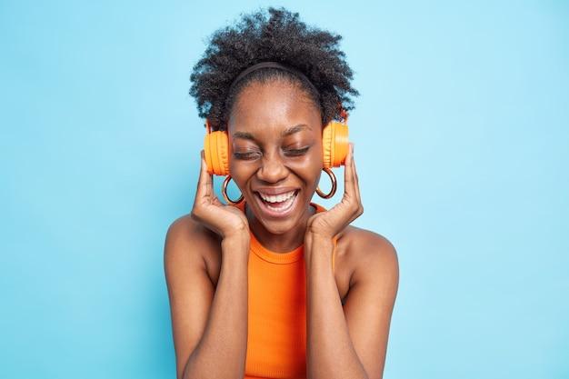 Optimistic dark skinned woman listens to  audio track via headphones