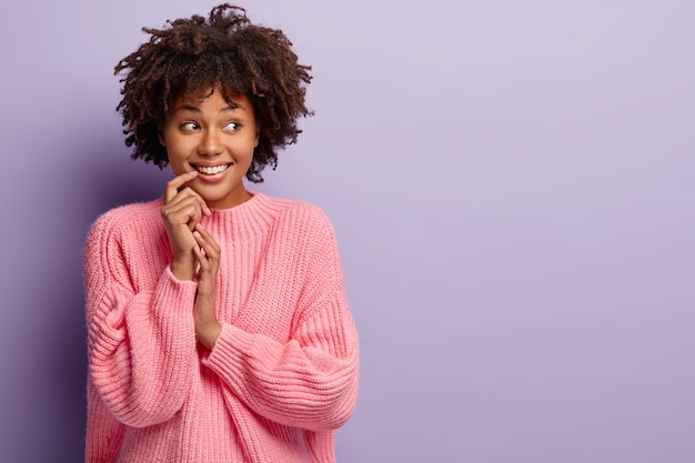 Optimistic dark skinned young female with crisp hair, smiles gently, keeps hand near mouth, looks dreamy aside, waits for something pleasant, wears pink jumper, isolated on purple wall